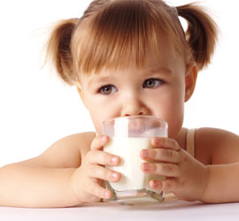 Little girl in pigtails drinking milk