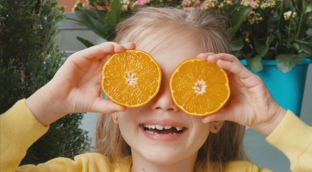 Girl holding orange slices in front of her eyes